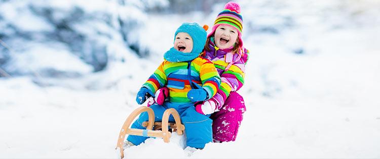 Zwei lachende Kinder auf einem Schlitten